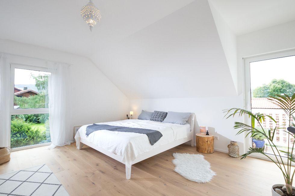 Lichtdurchflutetes Schlafzimmer mit Holzboden