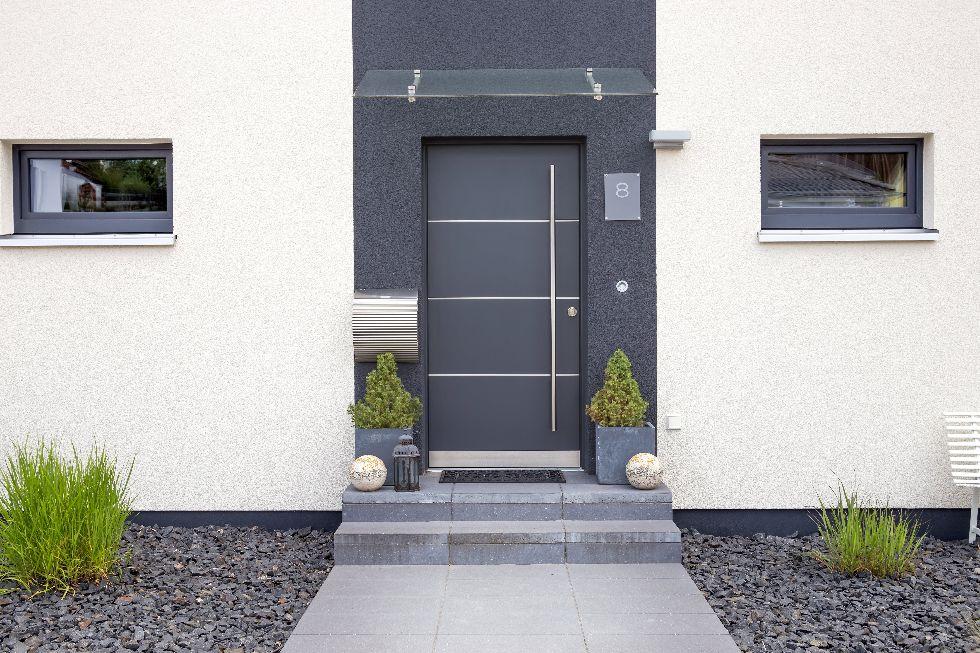Elegante graue Haustüre mit vertikalen Edelstahlstreifen