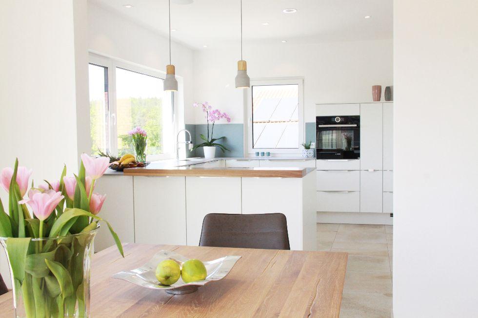 Klassisch elegante Küche mit Tresen und Natursteinplatte